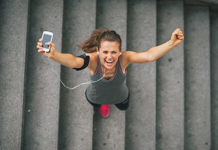 Portrait of happy fitness young woman with cell phone outdoors in the city rejoicing